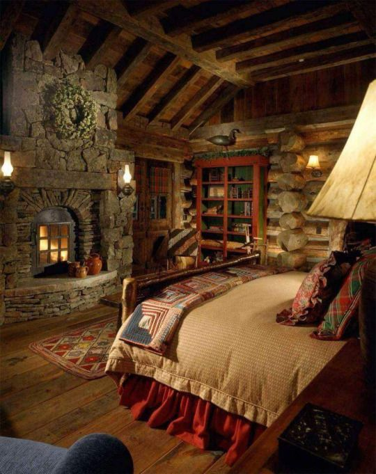 Log cabin home master bedroom with custom stone fireplace, exposed beams, salvaged wood flooring and luxe linens