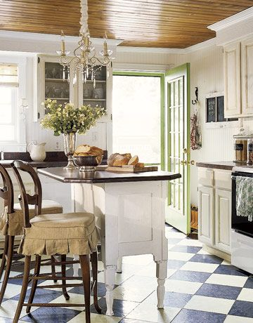 Loving this space, the lime green door, wood ceiling, chandelier, flooring, island, glass cabinets.