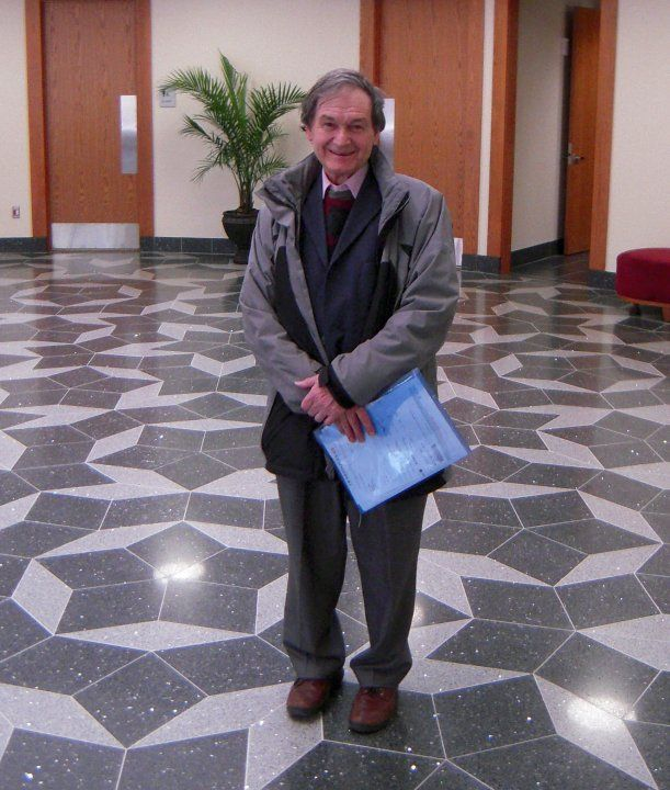 Roger Penrose in the foyer of the Mitchell Institute for Fundamental Physics and Astronomy, Texas A&M University, standing on a floor with a Penrose tiling.