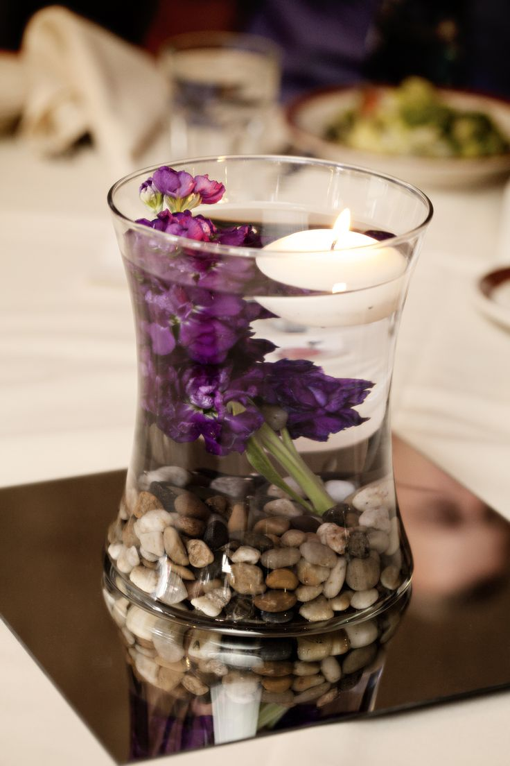 combine any size glass vase with river rock, a stem of live flower a floating candle and a mirror for reflection and you have a very romantic centerpiece for any intimate moment. Made the morning of the wedding.  Vase $5 Walmart, River rock $1 per bag at Dollar Tree, Candle less than $1 at Hobby Lobby, live flower stem $1.25 at local florist and pre owned 12 x12 mirror $1  Total $10