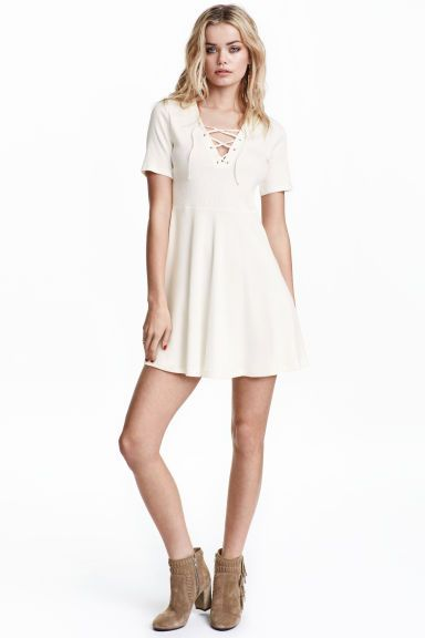 Ribbed dress with lacing: Short dress in ribbed cotton jersey with a deep V-neck with lacing at the front, short sleeves and a seam at the waist with a circular skirt. Unlined.