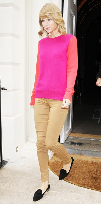 The singer added a pop of pink to her look in London in the form of a crewneck sweater worn with caramel-colored jeans and Miu Miu jeweled flats.