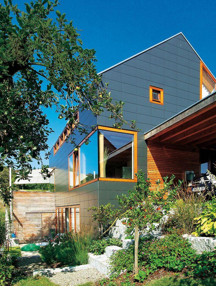 Die Bauherren wählten für die Außenhaut schieferdunkle Faserzementplatten - günstig wie auch unempfindlich. Die Fenster in lackierten Lärchenrahmen sitzen bündig in der Fassadenfläche.