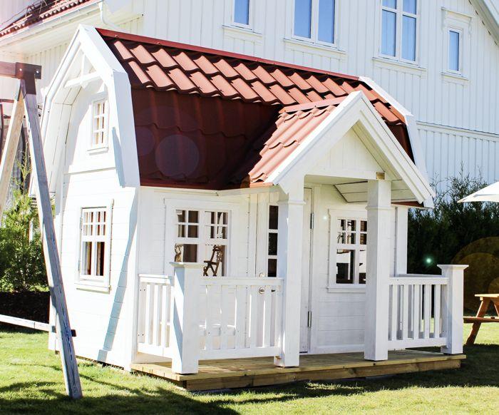 Lekstuga Djursholm Large (29 900 kr) med tillvalen Dörr med fönster (500 kr), Mellanpaketet innehållande takpanneplåt, blomlådor, fågelholk och öppningsbart fönster (6 500 kr) = 36 900 kr komplett. (omålad.) Här har kunden målat den i vit, valt röd takpanneplåt samt utsmyckat den med egen nockdekor.