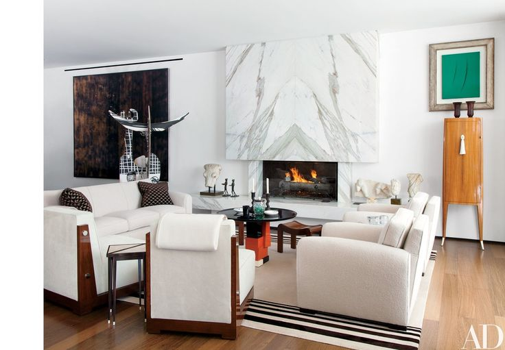 The living room of the 1960s Beverly Hills, California, home of Fernandez is furnished with a pair of vintage Jacques Adnet club chairs and a rosewood chiffonier by Émile-Jacques Ruhlmann, which is surmounted by a Lucio Fontana canvas. The Calacatta marble hearth displays two bronze cat sculptures by Diego Giacometti and several Roman marble fragments; the large sculpture at far left is by Aaron Curry.