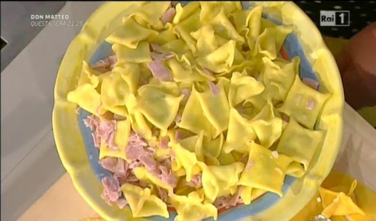 250 g di robiola, 250 g di mascarpone, 1 mazzetto di rucola  Per il condimento: 150 g di burro, 1 scalogno, 200 g di prosciutto cotto a fette, sale e pepe  Procedimento:  Facciamo la classica sfoglia impastando le uova con la farina. Tiriamo il panetto con il mattarello e la stendiamo. Tagliamo la sfoglia in piccoli rettangoli.  Per il ripieno in una ciotola mettiamo la robiola, il mascarpone, la rucola tritata. Amalgamiamo tutto e mettiamo in un sacco a poche.  Sopra ogni rettangolino