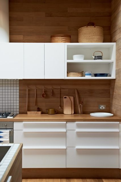 modern white cabinets with wood panelled walls in Pirates Bay House by O'Connor and Houle Architecture