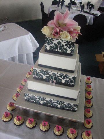 Extravagant black & white wedding cake with cupcakes