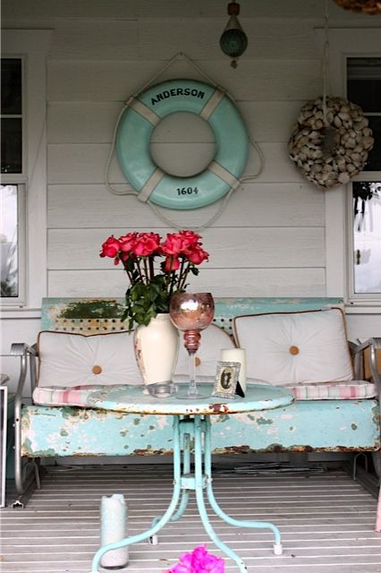 Diggin this beachy porch with distress blue glider and lifer-ring. I'd loose the shell wreath and just let it be
