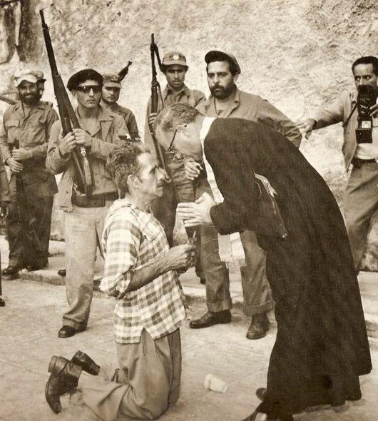 1960 - LAST RITES: A foto de Andrew Lopez (vencedora do Pulitzer), mostra um ex-membro do exército do ditador cubano deposto Fulgencio Batista, pouco antes de ser executado por um pelotão de fuzilamento de Fidel Castro. O condenado recebe os sacramentos finais.