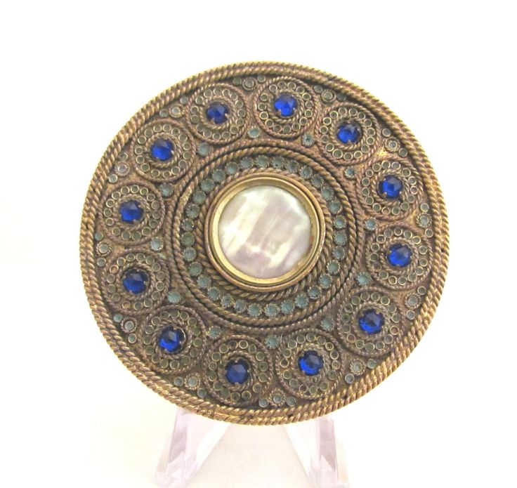 This is a gorgeous and very rare late 1800's French antique gold tone powder and rouge compact with a lovely central mother of pearl medallion surrounded by 12 blue stones. The lid has an extremely or
