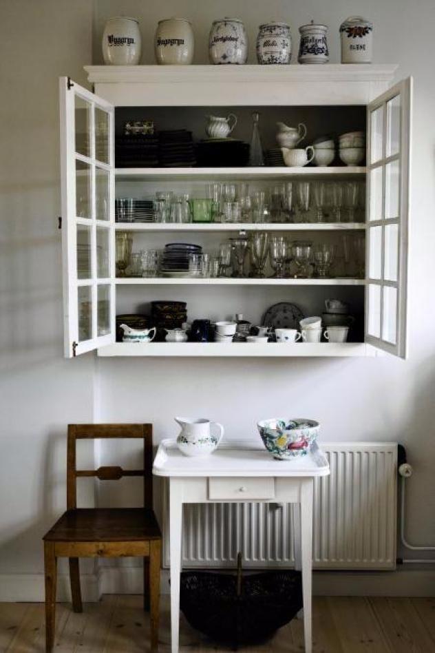 Vitrineskabet er fundet på et loppemarked. Hun har selv fået det slebet og malet hvidt, så det klæder et moderne køkken i stål og hvidt. Skabet er fyldt op med loppefund og arvestykker.