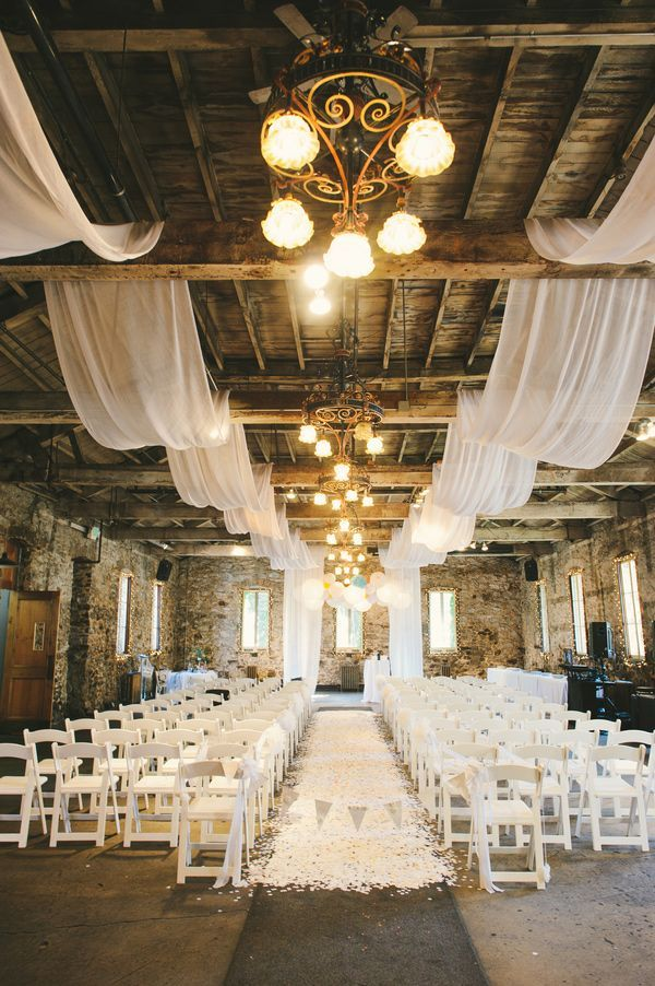 Barn wedding aisle with fabric draped ceiling and white flower petals