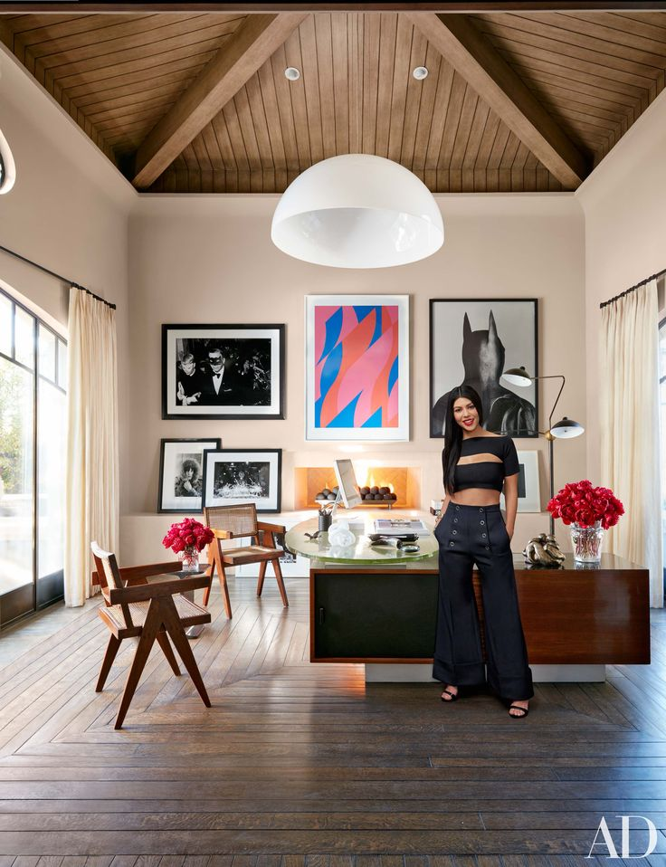Kourtney Kardashian in the home office of her California residence, which is furnished with a vintage Jules Leleu desk and Pierre Jeanneret chairs. | archdigest.com