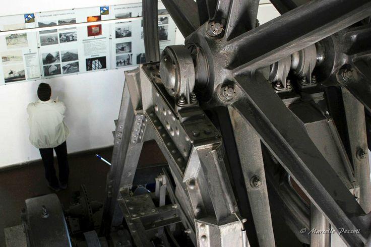 Funivia del Gran Sasso d'Italia, vecchia stazione d'arrivo: la grande ruota in disuso della prima funivia incombe minacciosa sull'uomo che guarda le fotografie di una mostra. Metafora dell'invadenza non percepita della tecnologia nella nostra vita.