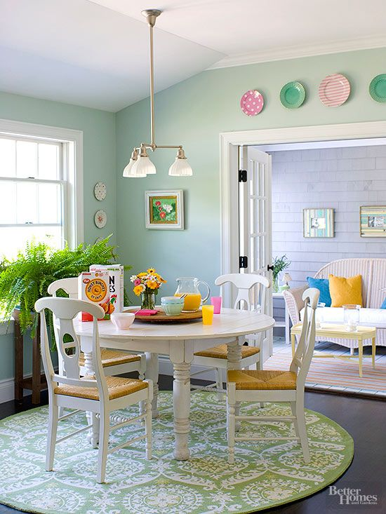 Pale green walls in this eating area add to the overall airy and feminine feel of the room. A worn-in white country table makes the room feel relaxed. The circular rug under the dining set brings pattern into the space and introduces a different shade of green. Plates hung above the door frame add more color and pattern as well./