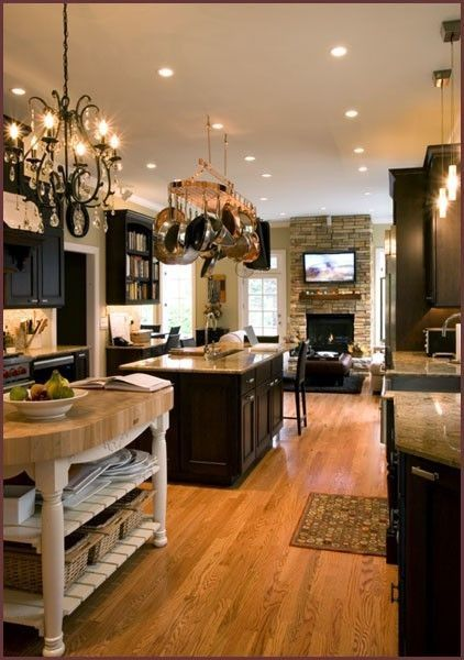 like the openness, pot rack, island with storage, fireplace in a living room, and chandelier for the dining room