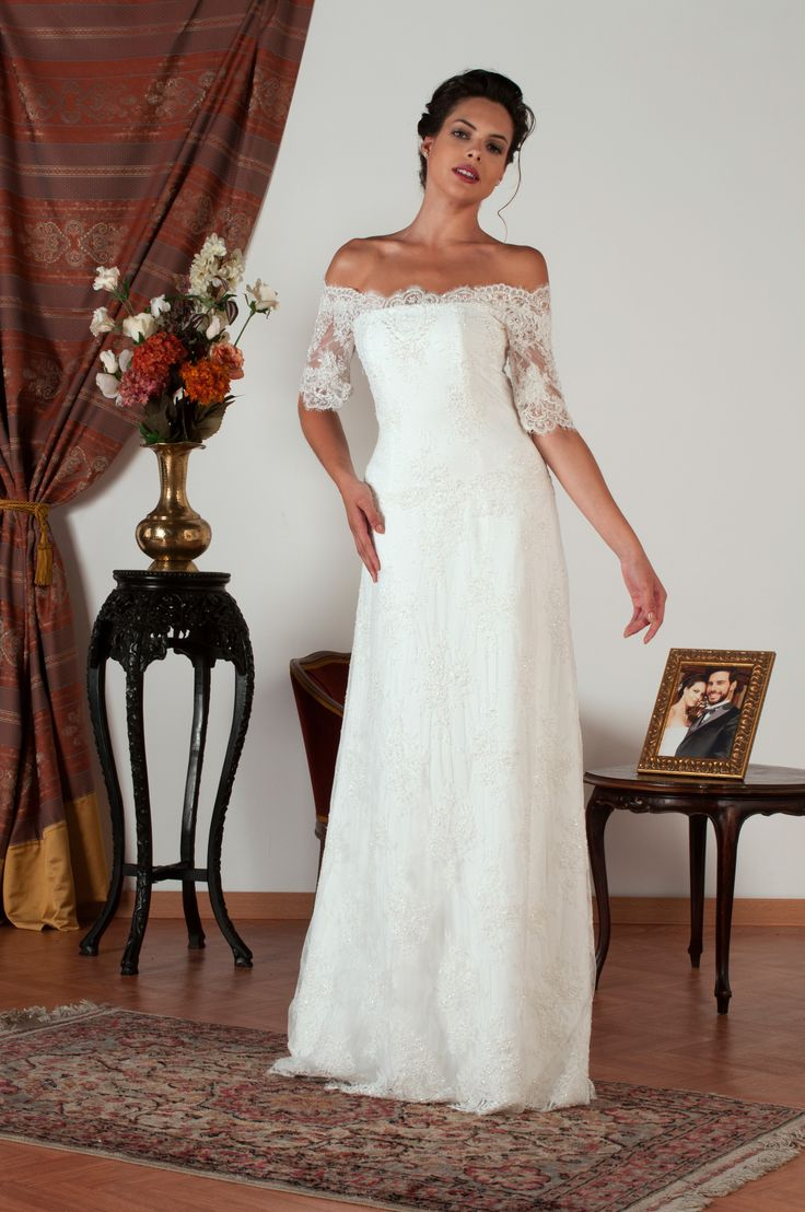 CAROLINE  Realizzato in pura seta e preziosissimo pizzo rebrodé interamente ricamato a mano con minuscole perline. / Silk wedding dress with beaded rebrode lace embroidery on the bodice. Cleavage on the back fastened with romantic hand-made silk covered buttons and the hand cut transparent lace continues onto the shoulders and arms to form three-quarter lace sleeves.