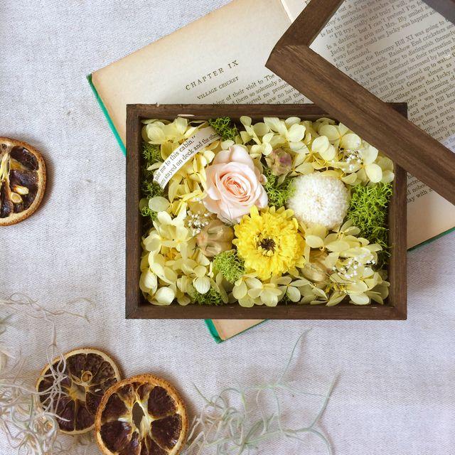 ダークブラウンに塗り込んだラスティック風の木箱。パッと元気になれるイエローをベースに、小花、木の実などをたくさん詰め込んだ、可愛らしいフラワーボックスです。蓋を開けて楽しむもよし、閉じて楽しむもよし。。。小さな宝箱のようなお花を楽しんでいただけたらと思い...