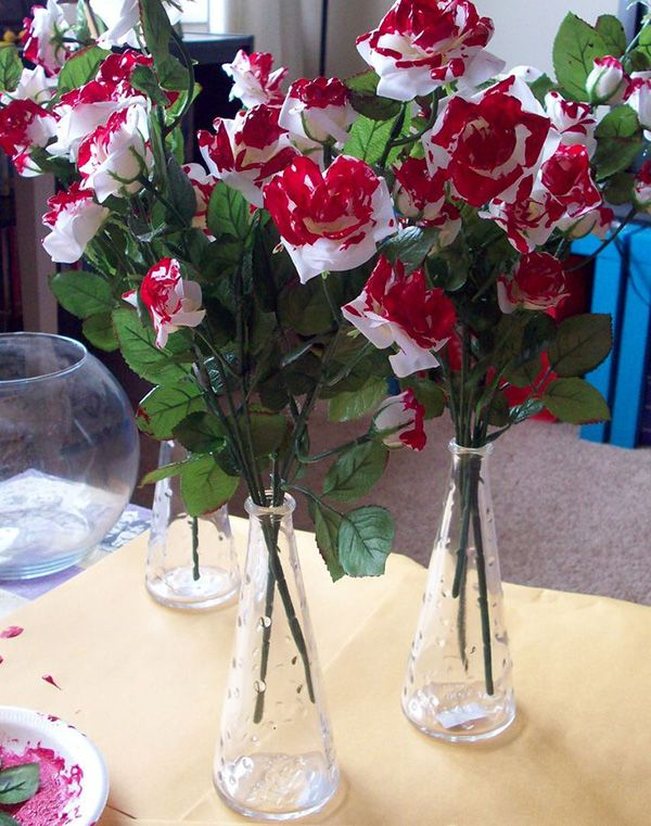 white roses painted red - a fun nod to the queen of hearts, but I would have put some filler in the vases or something here...