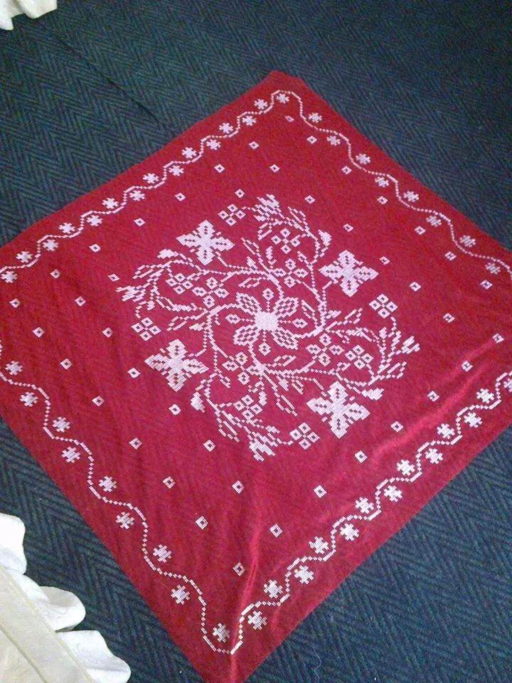 My stock cross-stitch pattern embroidered on the red shawl fabric. Source pattern is here: https://www.shutterstock.com/pic-127089347.html (design by Slanapotam)