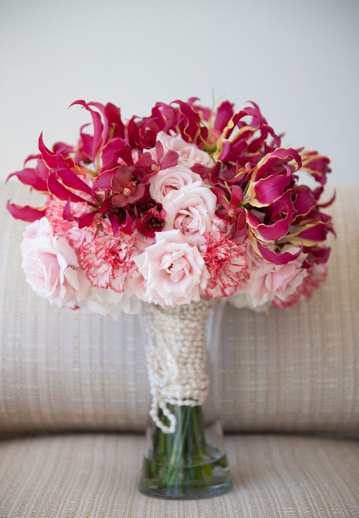 Unique pink bouquet with roses, carnations and orchids with pearl wrapped stems