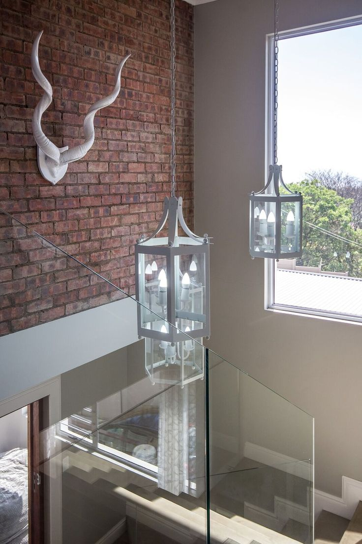 Modern crisp white lanterns over a double-volume staircase. To compliment this look, a glass staircase & exposed brick wall.
