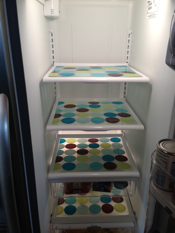Placemats used to line refrigerator shelves. Cut them to fit the shelf. This way if anything spills (which it will) you just take out the liner, wipe it clean, and put it back