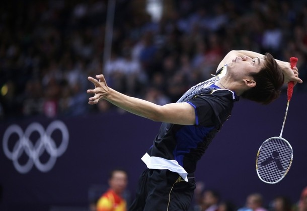 South Korea's Lee Yong-dae, rises up to smash a shuttle cock, against USA's Tony Gunawan and Howard Bach, unseen, at a men's doubles badminton match of the 2012 Summer Olympics,