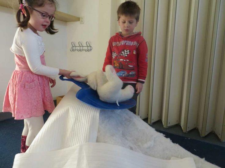 Leg een lap fiberfile in de bouwhoek op de grond. Dan lijkt het of er sneeuw ligt. Leg verder nog meer kleine en grote stukken in de hoek.Verder nog wat knuffels (poolhaas, ijsbeer, pinguïn), een klein sleetje en warme handschoenen. Laat de kinderen bergen en hellingen bouwen van de blokken. Daaroverheen kunnen ze het fiberfile leggen. Een wit fleece deken kan ook gebruikt worden. Daarna kunnen ze de knuffels op het sleetje van de helling laten gaan.