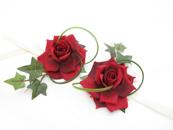 Two red classic rose wristlets. Find your perfect wedding flowers at www.loveflowers.com.au