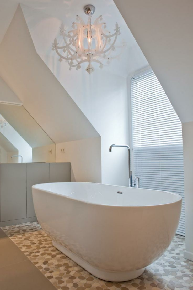 Beautiful white freestanding bathtub, accented with a white chandelier. Crisp and fresh!