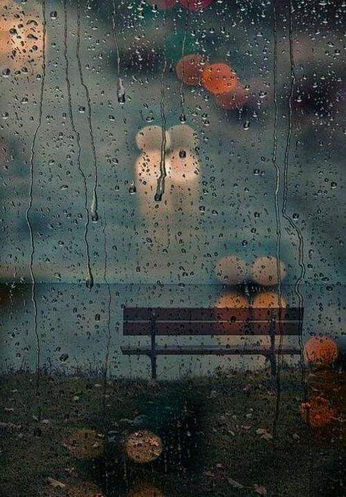 The point of focus of this image is interesting as it's not the bench or a full object. The raindrops on the window add some perspective to the blurred lights, middle ground, and background creating a contrast of sharpness.