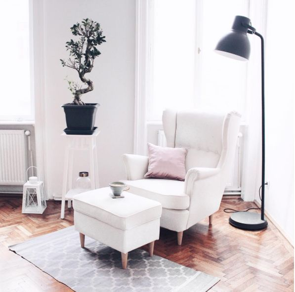 Wohnzimmer Ohrensessel in Weiß - gemütliche Leseecke mit Stehlampe. Dekoidee für schlichten weißen Raum: Eine originelle Zimmerpflanze, z. B. ungewöhnlich gewachsener Bonsai. Pflanze wird auf Beistelltisch richtig präsentiert.