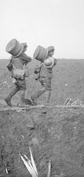 WWI, March 1917, near Pys; Troops of the Royal Engineers carrying reels of telephone wire going along a duckboard track. Detail. ©IWM Q 5003