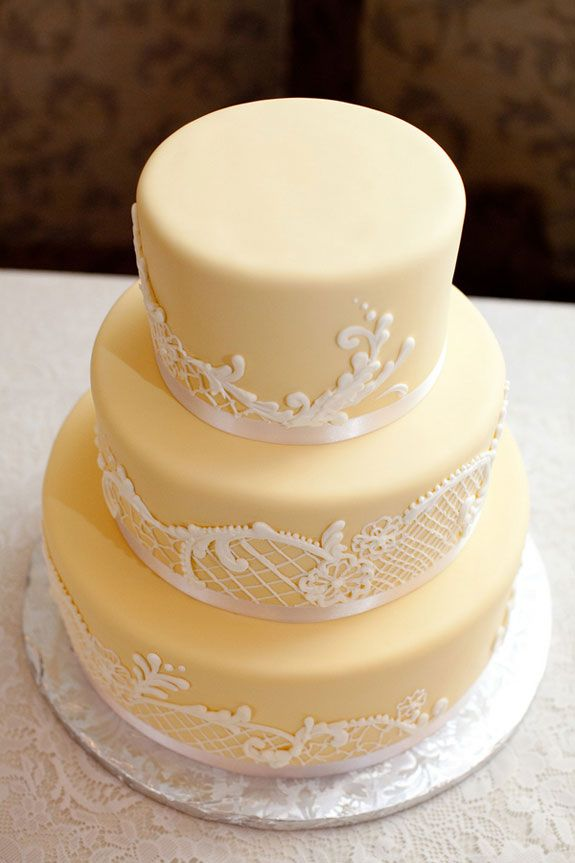 Stunning pale yellow wedding cake with lace trimmings...