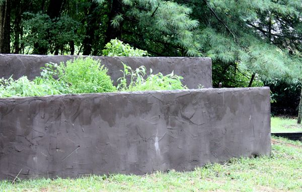Concrete block walls landscaping.  Cement stucco makes it look like poured concrete.  herb garden in summer.