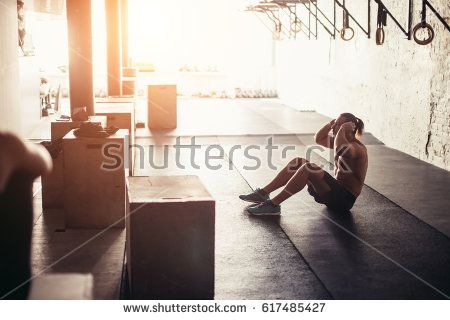 Sporty young male athlete on floor doing situps in gym. Fitness man doing abs crunches.