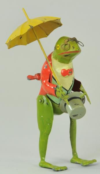 """ANTIQUE MECHANICAL FROG W/ UMBRELLA- Germany, early hand painted tin frog figure, holds umbrella and hat in hand, clockwork activates a wobbling motion. 7"""" h."""