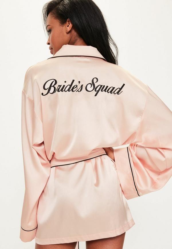 Cette robe de chambre rose avec broderies noires est faite pour montrer votre soutien à la mariée en cas d'enterrement de vie de jeune fille inopiné ! Du rose, du satin, une coupe courte, c'est girly à souhait et absolument parfait.