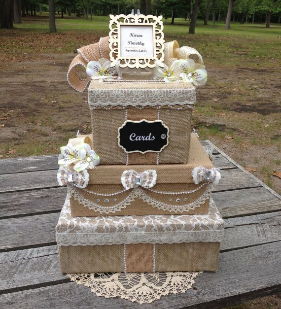 The Rustic Victorian Wedding Card Box has elegant lace and pearls decorating the simple burlap fabric that covers 3 tiers of boxes. The center box lid lifts off for retrieval of money envelopes after your reception. Handmade twine and pearl braid accent the box edges.  The top is decorated with a laser cut wooden frame and silk burlap white flowers with rhinestone centers. The frame will be personalized with your names and wedding date. A chalkboard cards sign is attached to the front. The…