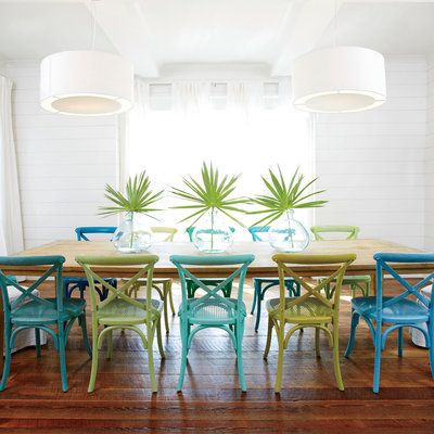 Creamy shiplap walls, mod white pendant lights, and ivory draperies channel bright seaside light, while reclaimed wood floors and a long wooden dining table give the crisp, just-built space a well-worn, well-loved feel.