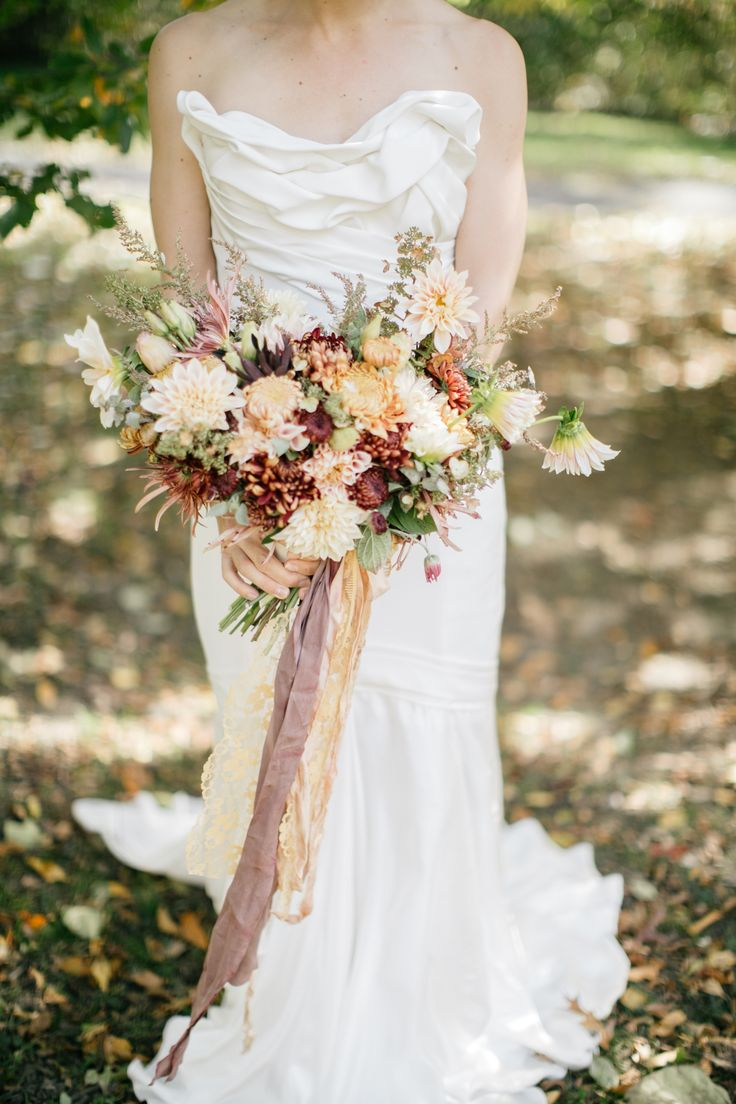 Late autumn bridal bouquet with antique mums and dahlias in muted tones of copper, garnet, and cream. Grown and designed by Love 'n Fresh Flowers. Photo by Emily Wren Photography. Gown by Carol Hannah.