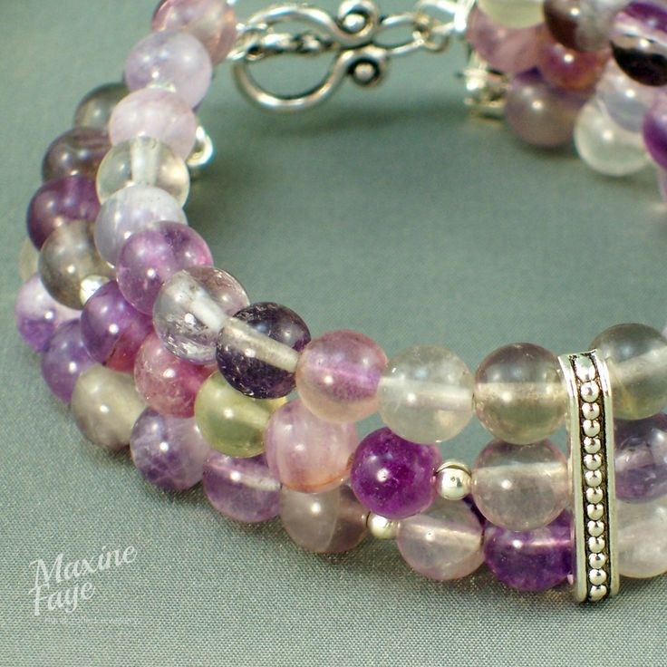 66 x approx 6mm Rainbow Fluorite round beads and smooth silver spacers make up this triple strand bracelet.  Antiqued silver-plated spacer bars with a centre line of dots and a similar toggle clasp complete the design.  The total length is approx 22cm and findings are silver-plated.  https://www.maxinefaye.com.au/product-category/bracelets/