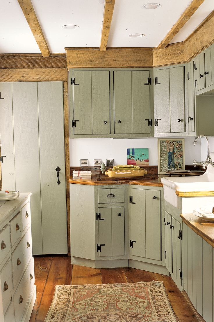 New, green cabinets in this old farmhouse kitchen are outfitted to look like they could be the originals.
