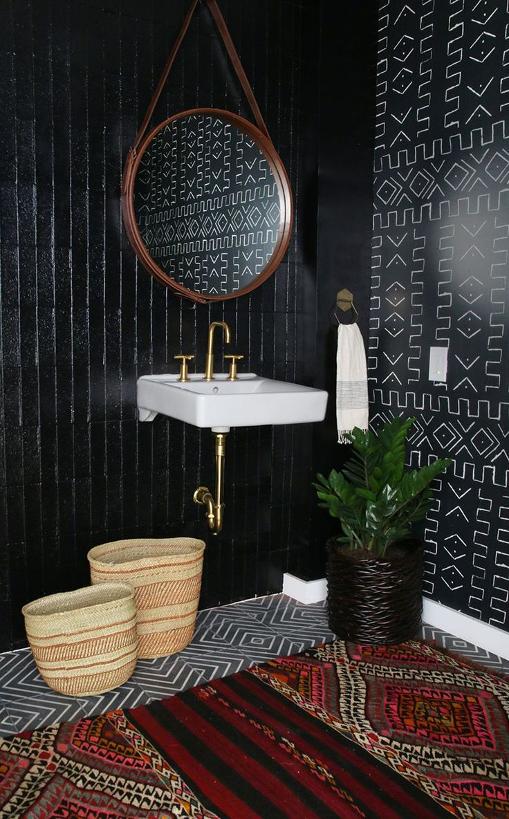 Don't be afraid to use dark colors in a small space. Natural accessories balance this bold bathroom from Amber Interiors.