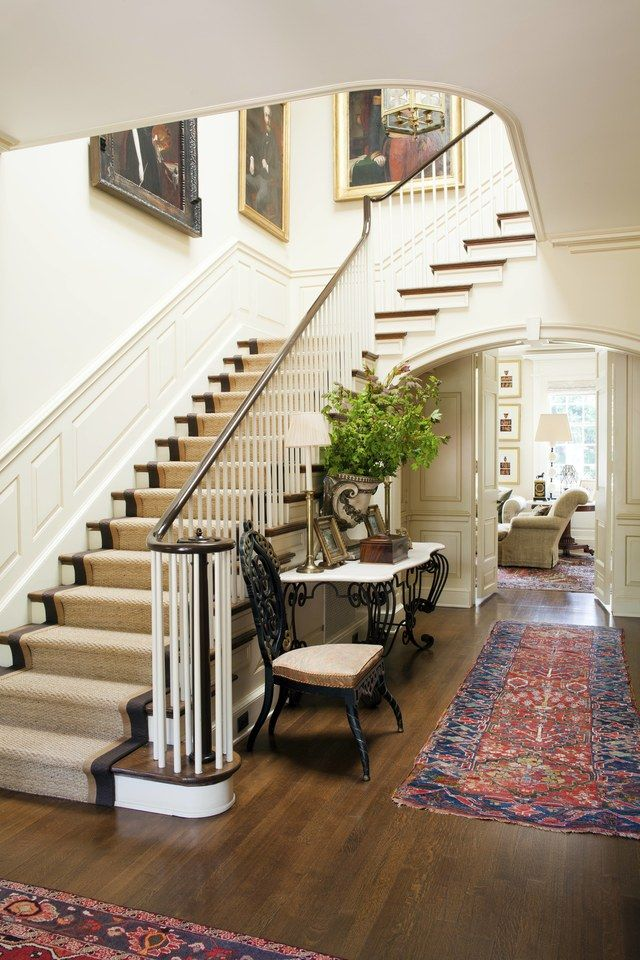 The palm grass carpets, finished with a leather border, that climb the stairs in this Timothy Corrigan home are a classic contrast to the Oriental rugs on the first floor.