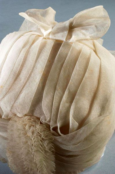 Immaculate Widow's cap with pleated top and sides, made of white woven silk or wool crape. The front of the cap is edged with rows of narrowly pleated crape. There is a large crape bow at the pointed centre front of the cap, and a large crape pom-pom at the back. (picture: Mandy Reynolds): 1870S Cap, Appropriate, Woven Silk, Victorian Time, Correction, Centres Front, Bows, Pleated Tops, 1870 S