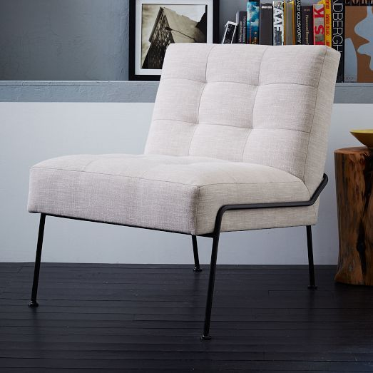 Comfortable buttonless tufted cushions and a slim metal frame give the Oswald Slipper Chair a clean, contemporary silhouette.