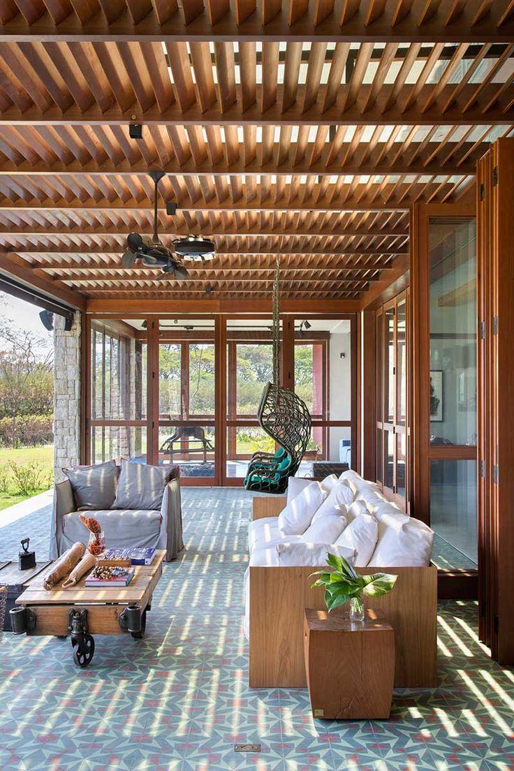 Decoração de casa de campo simples e integrada com a natureza. Na varanda, sofá de madeira com estofado branco, poltrona cinza, plantas, cadeira de balanço e mesa de centro. #decoracao #decor #design #details